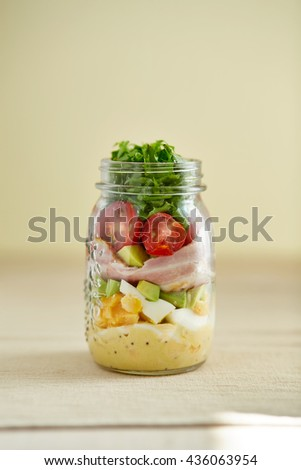 avocado, ham, tomatoes , eggs, sauce and rocket leaves in the jar agains ivory color background - stock photo