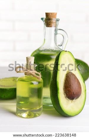 Avocado oil on table on light background - stock photo