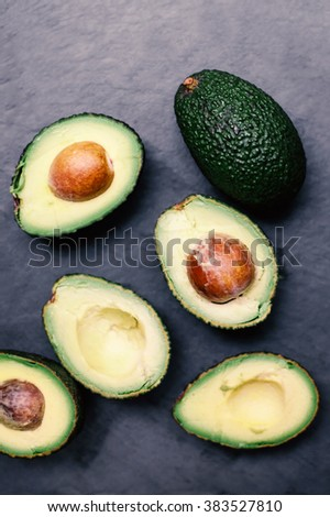 Avocado on a black background, top view image. Halved avocado, close up with copy space - stock photo