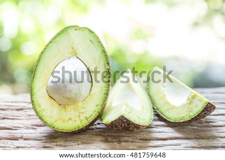 Avocado on a wooden floor and has a background of nature