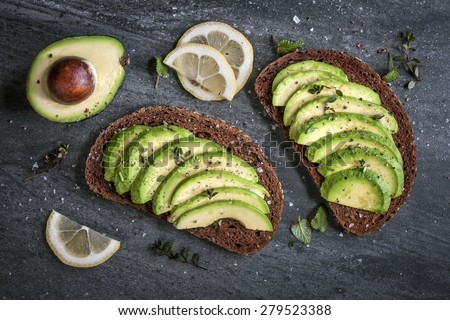 Avocado sandwich on dark rye bread made with fresh sliced avocados from above - stock photo
