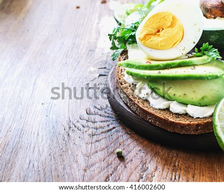 Avocado sandwich with dark rye bread, cream cheese and egg on a dark brown board, Selective focus. Healthy concept. - stock photo