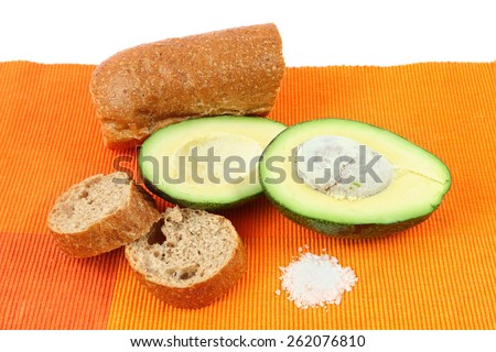 Avocado, sliced rye bread  and salt on a bright color napkin. - stock photo
