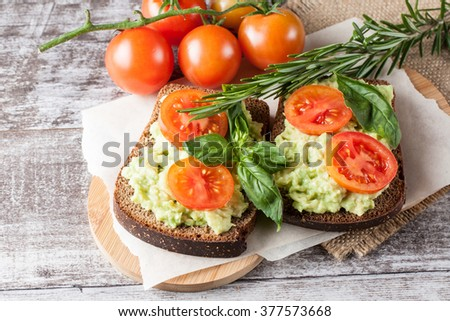 Avocado toast, cherry tomato on wooden background. Breakfast with toast avocado, vegetarian food, healthy diet concept.  - stock photo