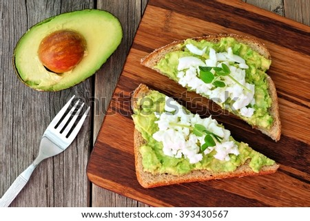 Avocado toast with egg whites and pea shoots on wooden board, overhead view