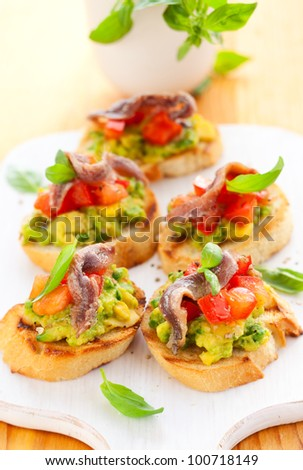 avocado,tomato and anchovy crostini on cutting board