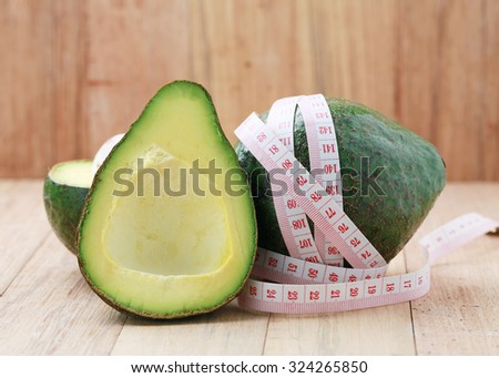 Avocado with a tape measure on a wooden table.The concept of weight loss.Dieting. - stock photo