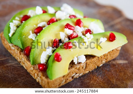 Avocado with Feta, pomegranate and olive oil on sunflower seeds bread sandwich. Healthy organic and vegan breakfast, on wooden background - stock photo