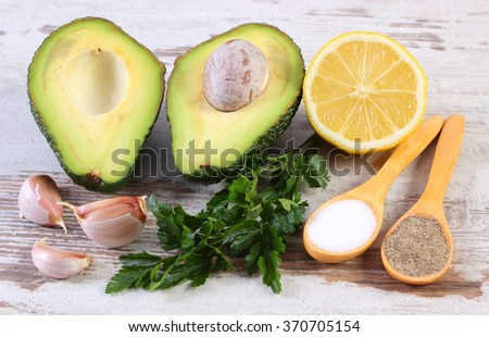 Avocado with ingredients and spices to avocado paste or guacamole, garlic, lemon, parsley, concept of healthy food, nutrition and omega fatty acids - stock photo