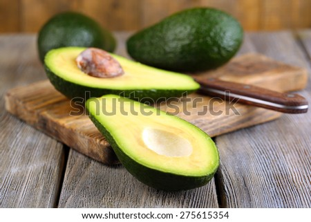 Avocado with knife on cutting board on wooden background - stock photo