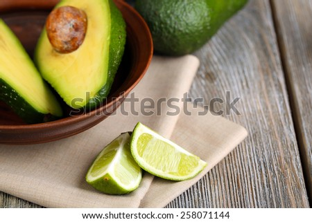 Avocado with limes in bowl on table close up