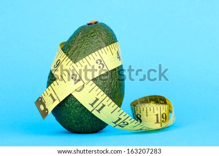 avocado with measuring tape on blue background