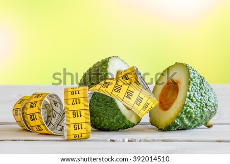 Avocado with yellow measure tape on a table - stock photo