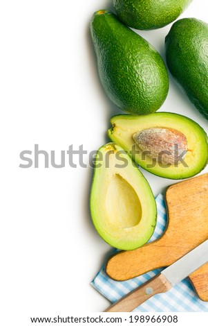Avocados with knife and cutting board - stock photo