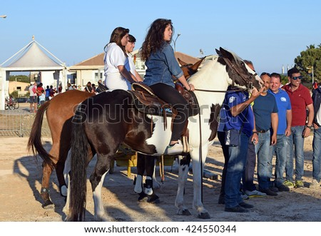 Avola, IT - May 22, 2016: People riding horses and enjoying talking with the audience. They're partecipating in an equestrian event. - stock photo