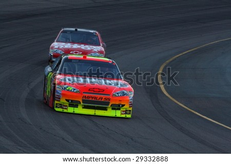 AVONDALE, AZ - APRIL 18: Jeff Gordon (24) leads Tony Stewart (14) out of turn two in the NASCAR Sprint Cup Series race at Phoenix International Raceway April 18, 2009 in Avondale, AZ. - stock photo
