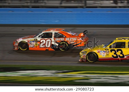 AVONDALE, AZ - APRIL 18: Joey Logano (20) tries to stay ahead of Clint Bowyer (33) in the NASCAR Sprint Cup Series race at Phoenix International Raceway April 18, 2009 in Avondale, AZ. - stock photo