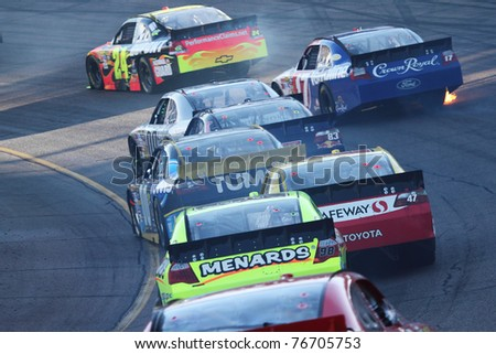 AVONDALE, AZ - NOV 14: Jeff Gordon (24) leads a group of cars in the Kobalt Tools 500 race on Nov 14, 2010 at the Phoenix International Raceway in Avondale, AZ. - stock photo