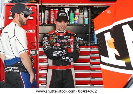 AVONDALE, AZ - OCT 4: Jimmie Johnson (left) and Jeff Gordon talk in the garage during a track testing session on Oct. 4, 2011 at Phoenix International Raceway in Avondale, AZ. - stock photo