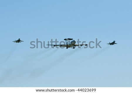 awacs in flight guarded by two Mig 29s against blue sky