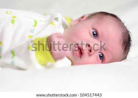 Awake Infant with Blue Eyes. Three-week old baby boy laying on white blanket. Shallow DOF.