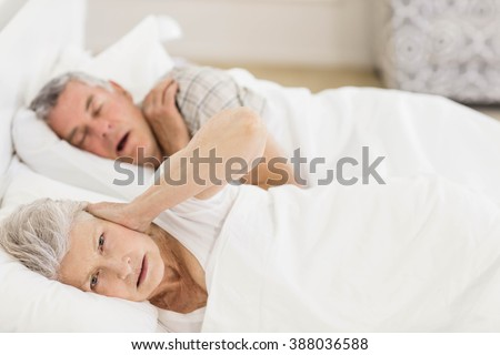 Awake senior woman in bed covering her ears while her husband is snoring - stock photo