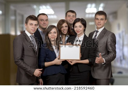Awarded business team. Business team of seven members just received the award for achievement and expresses pride and happiness. The frame they keep is blank, you may easily insert any text you want. - stock photo