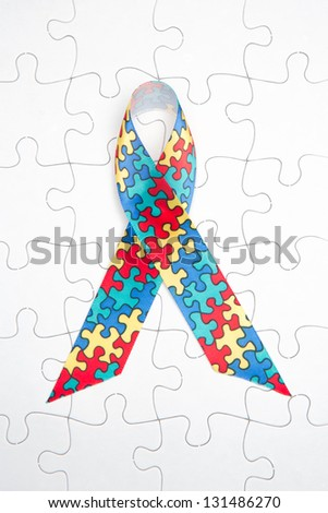 Awareness ribbon for autism and aspergers on white jigsaw background - stock photo