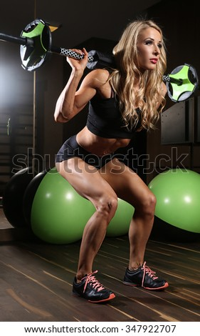 Awesome blond fitness woman doing legs exercise with barbell.