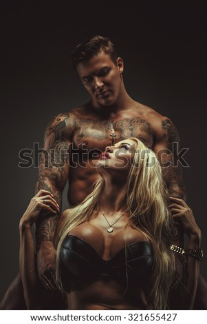 Awesome blond woman in underwear and shirtless muscular man with tattoes isolated on grey bachground.