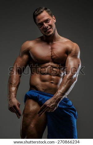 Awesome bodybuilder in deep shadows posing in studio. Isolated on grey