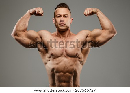 Awesome bodybuilder posing in studio on grey background.