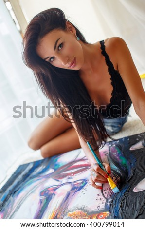 Awesome brunette woman painting on the floor. - stock photo