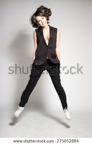 Awesome caucasian attractive joyful happy sexy dance model is jumping in studio wearing suit and shoes isolated on gray background - stock photo