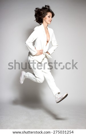 Awesome caucasian attractive joyful happy sexy dance model is jumping in studio wearing white suit on gray background - stock photo