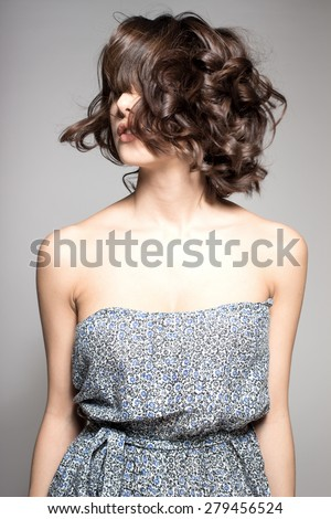 Awesome caucasian attractive joyful happy sexy female model is shaking head with brunette hair in studio wearing nice dress, isolated on gray background - stock photo