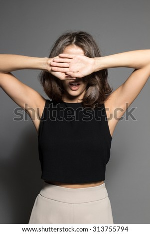 Awesome Caucasian attractive joyful happy sexy female model is shaking head with brunette hair in studio wearing black sleeveless shirt, isolated on gray background - stock photo