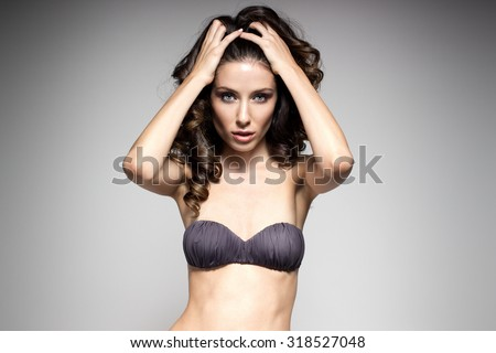 Awesome caucasian attractive sexy fashion model in lingerie with long brunette natural hair, beautiful eyes, full lips, perfect skin posing  in studio, beauty photo shoot, retouched image - stock photo