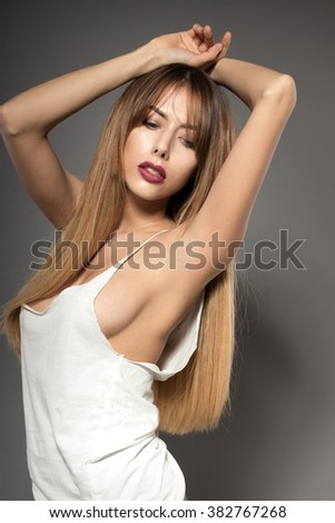 Awesome caucasian attractive sexy fashion model with extended hair posing in studio in white shirt, perfect make up, tanned skin, isolated on grey background, retouched image - stock photo