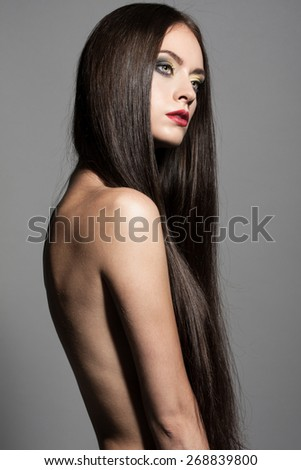 Awesome caucasian attractive sexy fashion model with long brunette natural hair, beautiful eyes, full lips, perfect skin posing topless in studio for beauty photo shoot, retouched image - stock photo
