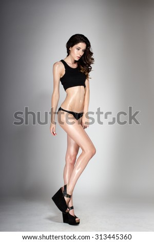 Awesome caucasian attractive sexy fashion model with natural brunette hair, long legs, perfect skin, wearing black shoes, panties and sleeveless sports shirt, beauty photoshoot, retouched image - stock photo