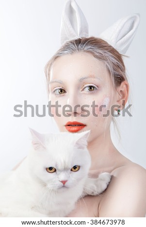 Awesome caucasian attractive sexy fashion model with red (ginger)l hair, beautiful eyes, full lips, perfect skin posing in studio, holding white cat, beauty photo shoot, retouched image - stock photo