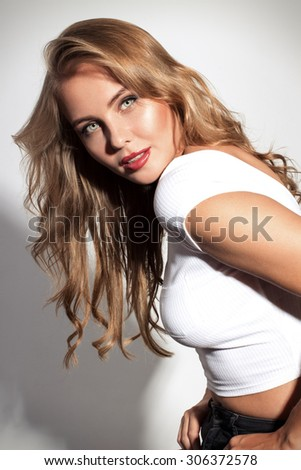 Awesome caucasian attractive sexy professional female model with blond hair posing in studio wearing white shirt and black ripped jeans, smiling, isolated on white background - stock photo
