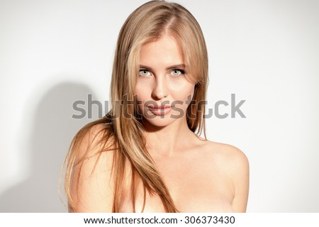 Awesome caucasian attractive sexy professional female model with blond hair posing in studio topless, perfect make up, tanned skin, isolated on white background - stock photo
