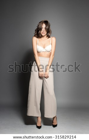 Awesome Caucasian attractive shy sexy female model with brunette hair posing in studio, wearing awesome transparent lingerie, isolated on gray background - stock photo