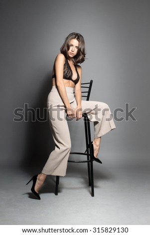 Awesome Caucasian attractive shy sexy female model with brunette hair posing on chair in studio, wearing awesome transparent lingerie, isolated on gray background - stock photo