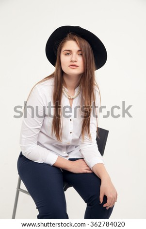 Awesome Caucasian attractive shy sexy female model with brunette hair posing on table in studio, wearing formal suit and hat, isolated on white background