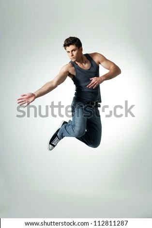 awesome dancer is jumping very high on light background