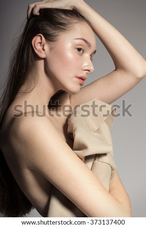 Awesome European attractive sexy fashion model with natural brunette hair, long eyelashes, full lips, perfect skin, posing in studio, holding beige coat, beauty photo shot, retouched image - stock photo