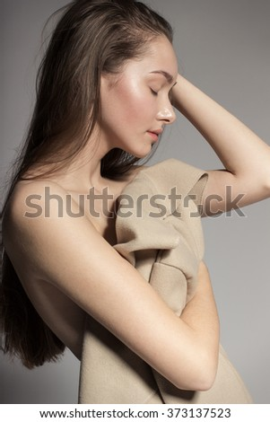 Awesome European attractive sexy fashion model with natural brunette hair, long eyelashes, full lips, perfect skin, posing in studio, holding beige coat, beauty photo shot, retouched image